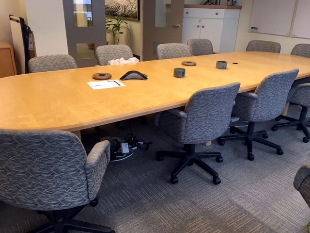Photo of a conference table surrounded by empty chairs